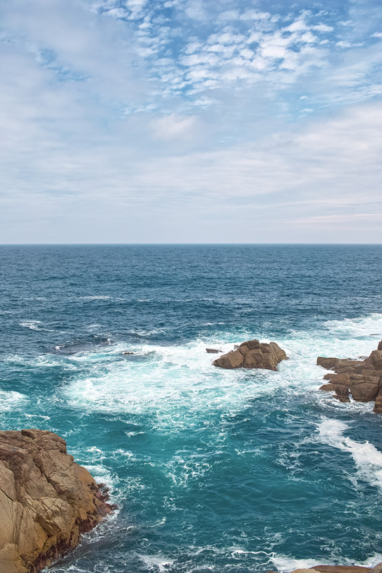 磯の岩場に砕ける波の写真画像
