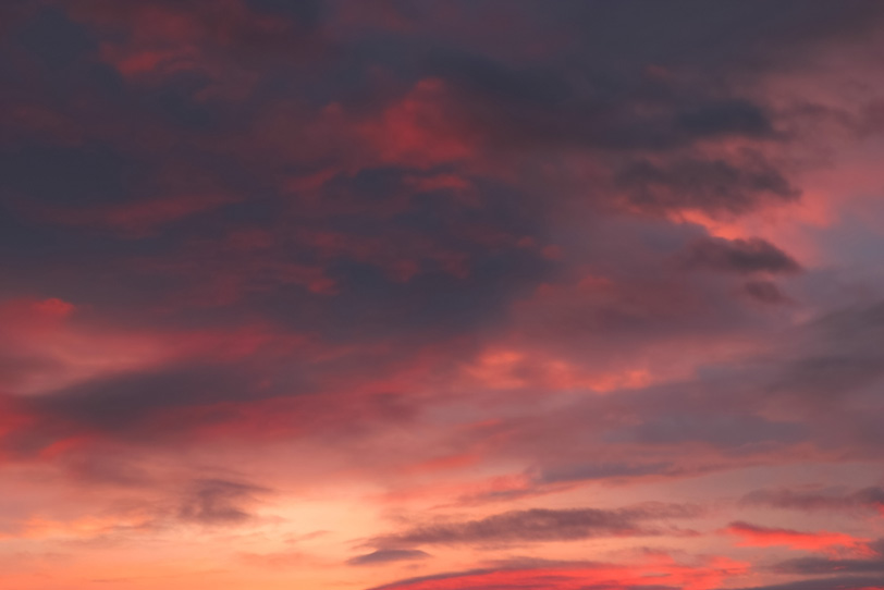 灰色の雲に反射する夕焼けの朱色の写真画像