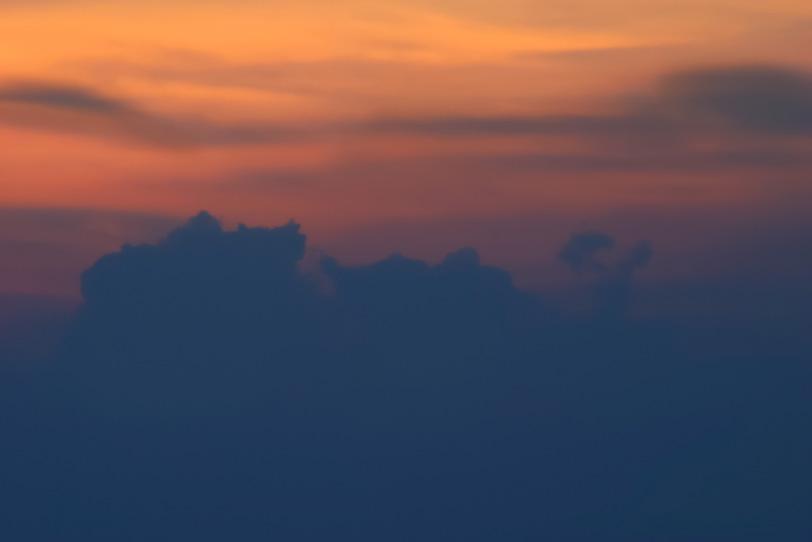 墨色の雲とオレンジ色の夕焼けの写真画像