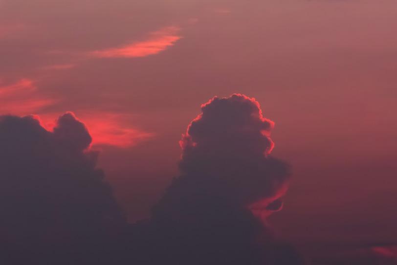 雲のシルエットを照らす夕焼けの光の写真画像