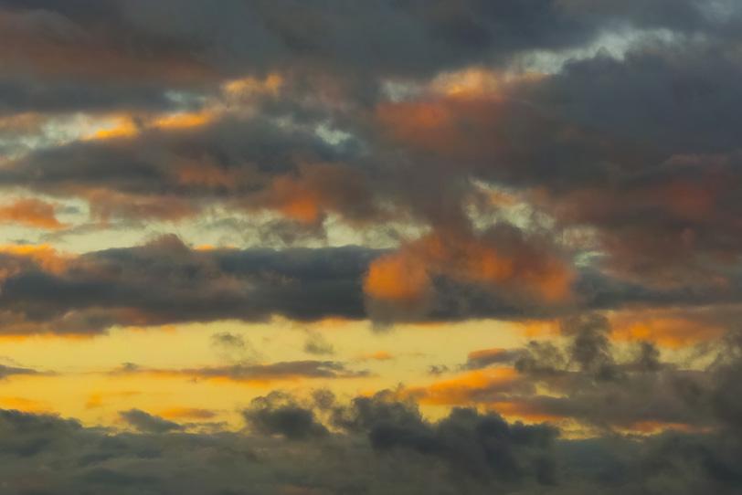 灰色の雲が滲む夕焼けの写真画像