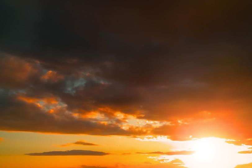 沈む夕日と夕焼けに焦げた雲の写真画像
