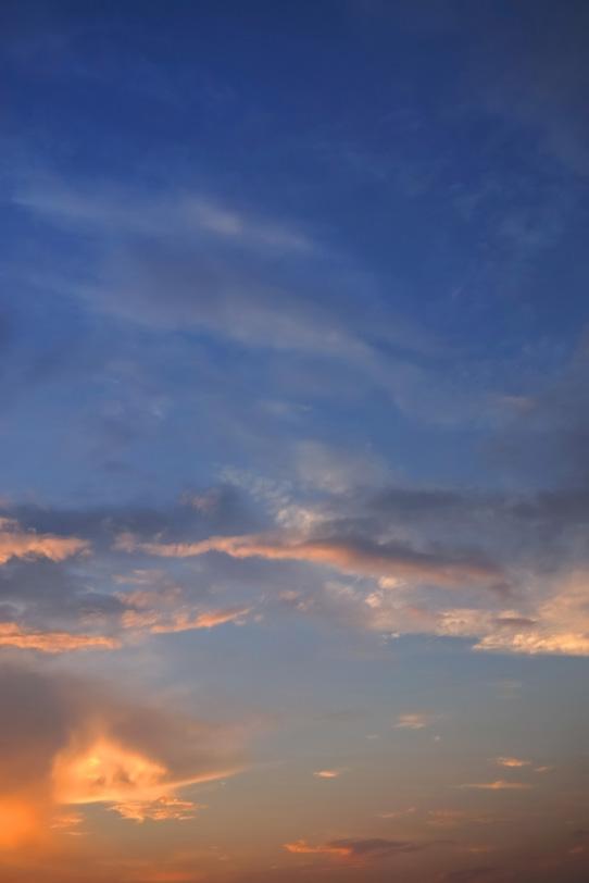 雲を夕焼けの光が照らすの写真画像