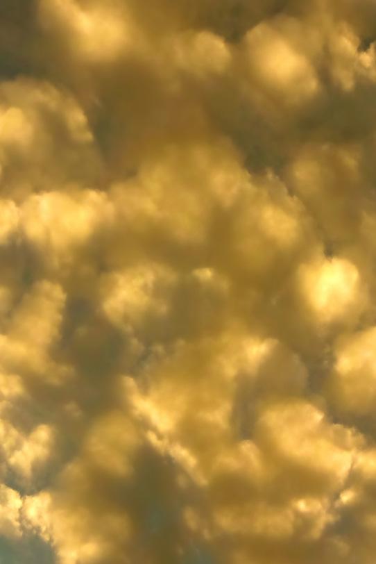 金色に輝く丸い雲と夕焼けの空の写真画像
