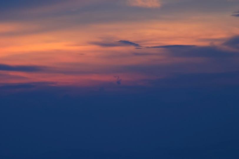 朱色の夕焼け空に青藍が滲むの写真画像
