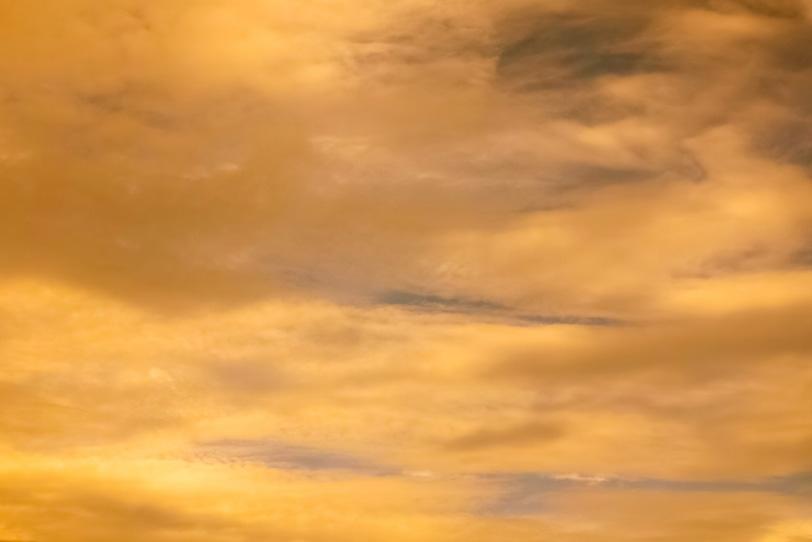 夕焼けに彩られる金色の空の写真画像
