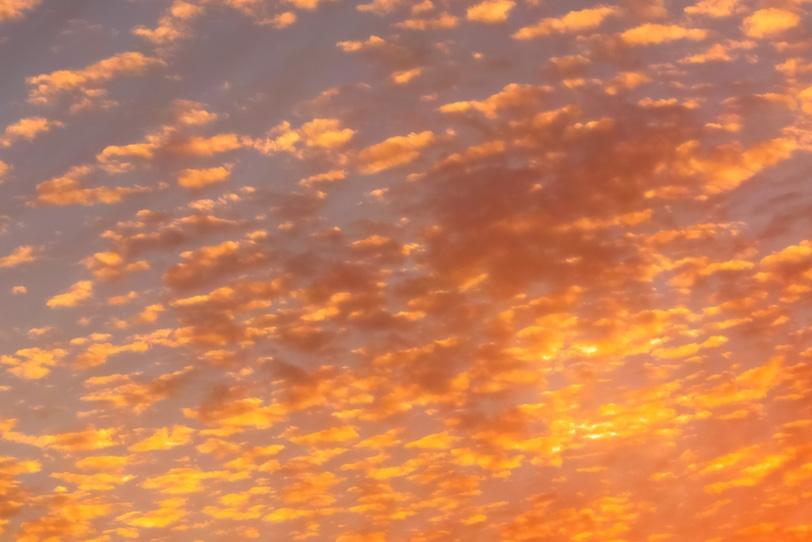 無数の雲が橙色に染まる夕焼けの写真画像