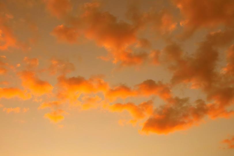 夕焼けの空を飾る橙色の雲の写真画像
