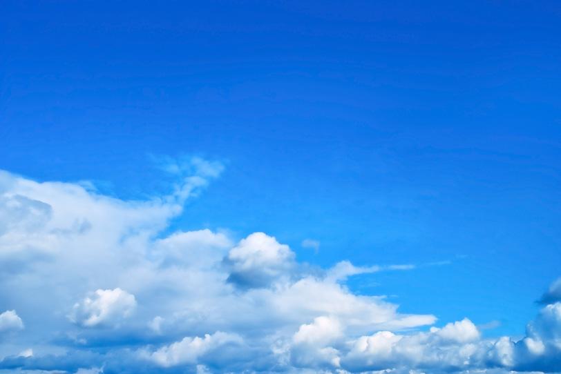 青空の下を這う積雲と濃密雲の写真画像