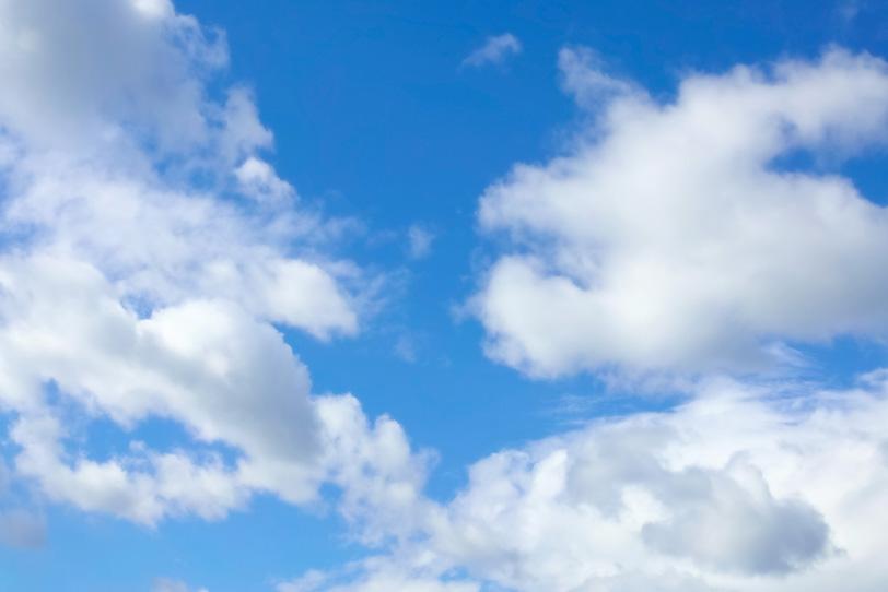 青空に白い綿が舞うような雲の写真画像