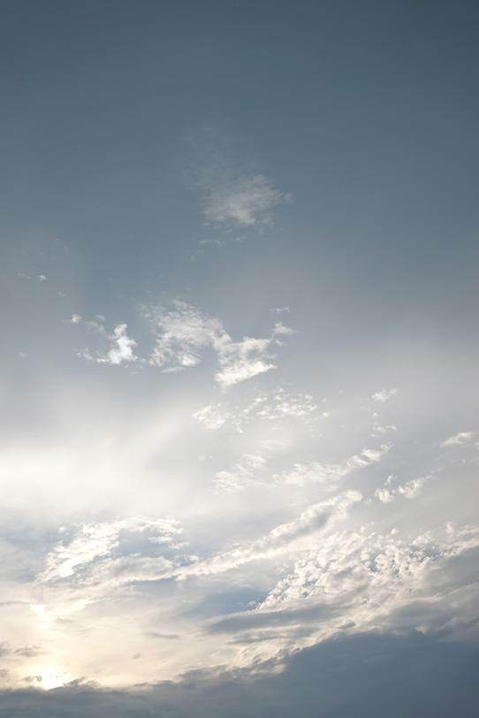 灰色の空に光り輝く雲の写真画像