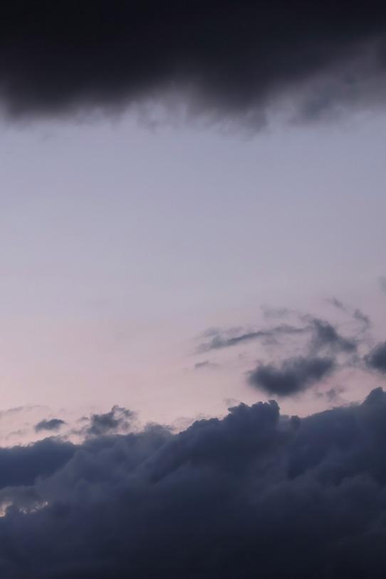 淡い夕焼けが暗雲の間に見えるの写真画像