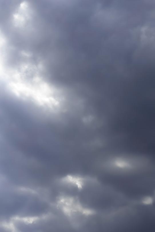 空の暗雲から漏れる光の写真画像
