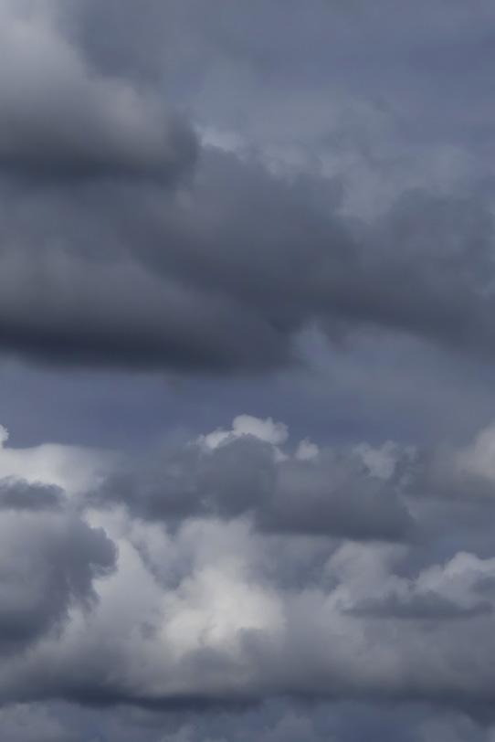 厚い雨雲が重なる暗い空の写真画像