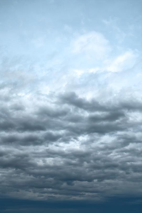 薄曇りの空に叢雲が押し寄せるの写真画像