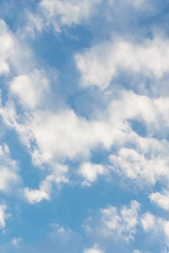 白雲がぼやけて滲む青空の写真画像