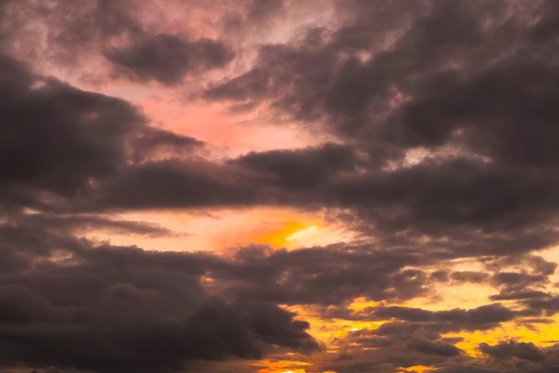 夕焼けの空に黒い雲が覆うの写真画像