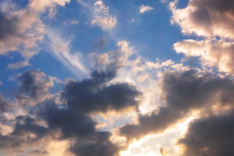 雲が色づき輝く暗い青空の写真画像