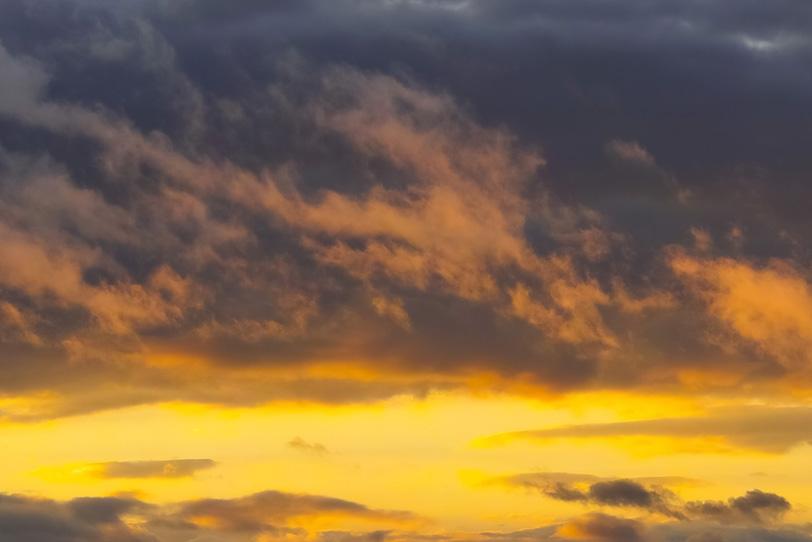 黄金色に輝く夕焼けと黒雲の空の写真画像