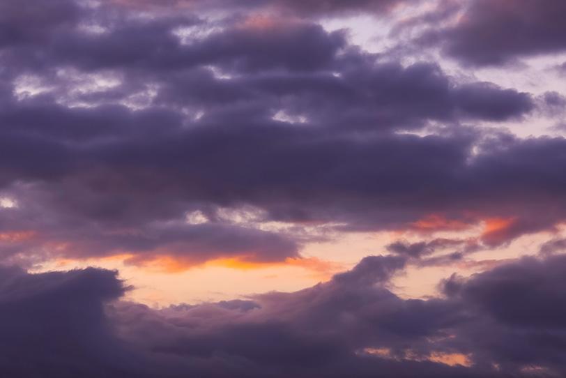 夕焼けの空に重なる深紫の雲の写真画像
