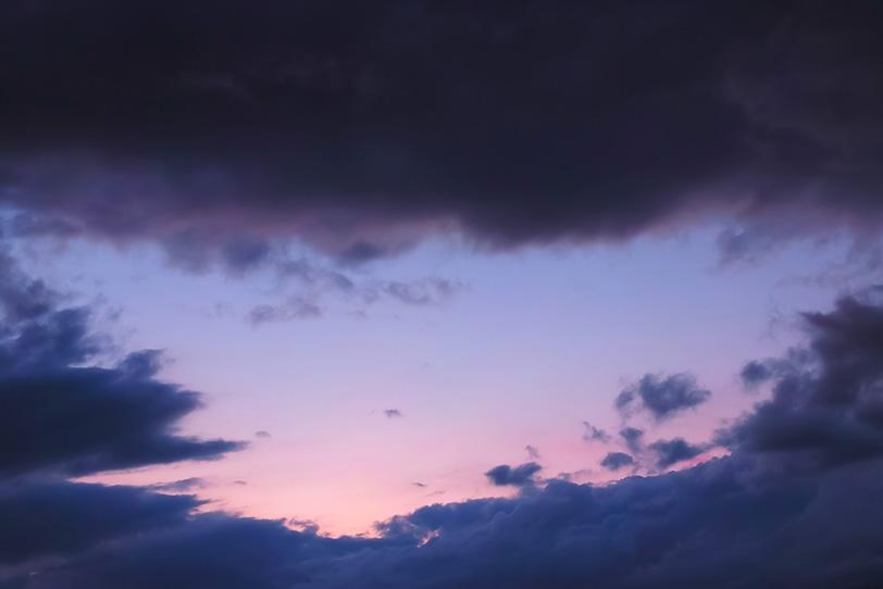 黒雲が囲む淡い夕焼けの写真画像