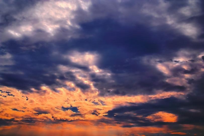 鮮烈な炎と黒煙のごとき夕焼けの写真画像