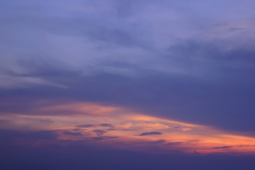 薄暗い夕焼けに黄丹色の光が伸びるの写真画像