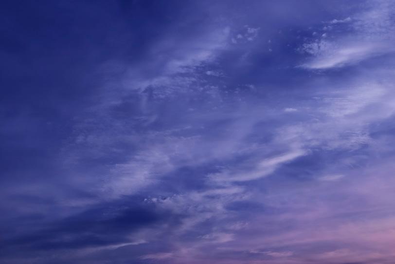 青紫色の雲を夕焼けが染めるの写真画像