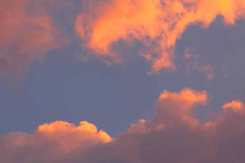 夕焼けに橙色の雲が踊るの写真画像