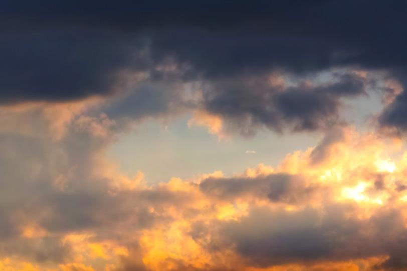夕焼けの雲に黒と橙が混ざるの写真画像