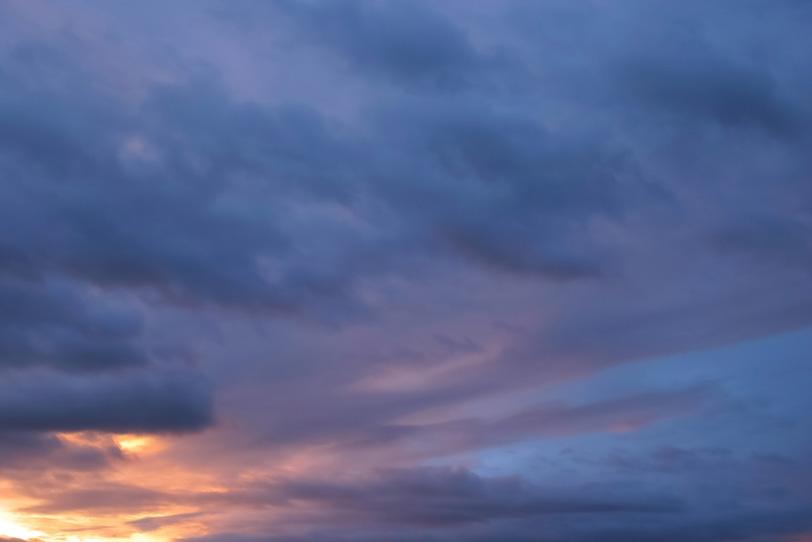 群青色の空を夕焼けの光が照らすの写真画像