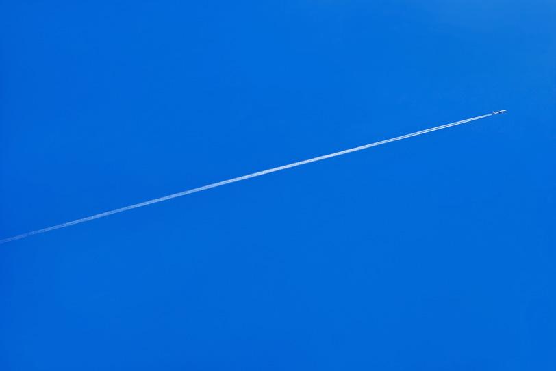青空に一直線を描く飛行機雲の写真画像