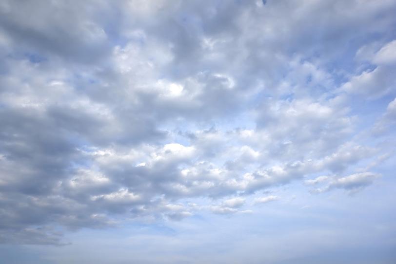 雲が押し寄せる薄く曇った青空の写真画像