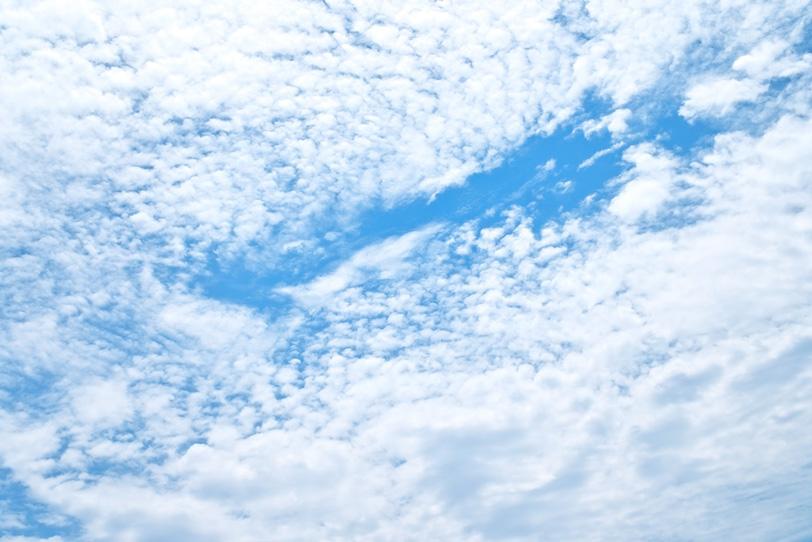 雲の谷間を流れるような青空の写真画像