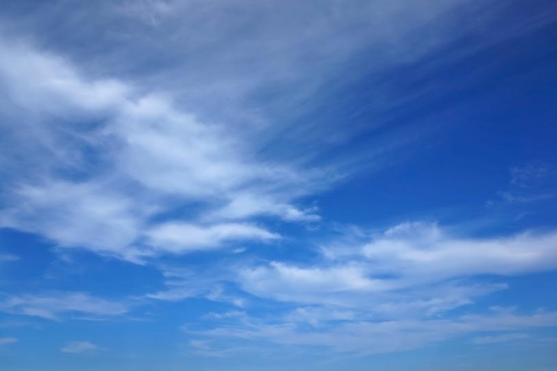 青空に筋を描きながら流れる雲の写真画像