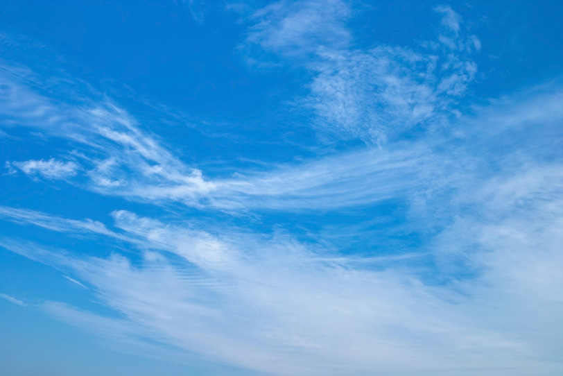 青空に尾を引いて流れる雲の写真画像