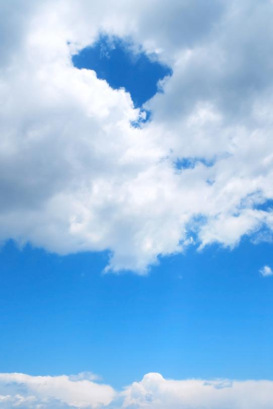 青空に浮かぶ穴の空いた雲の写真画像