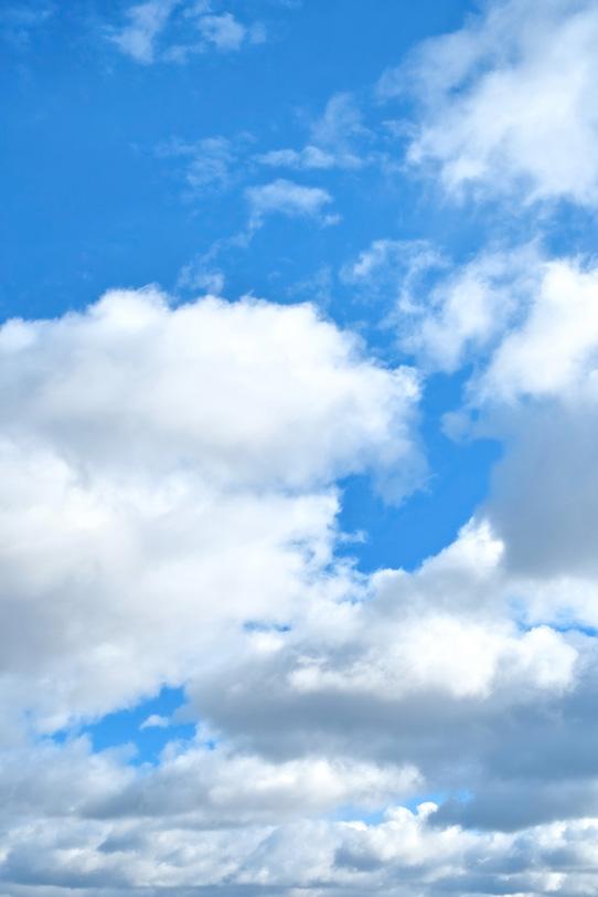 青空の下に群れ集う大きな雲の写真画像