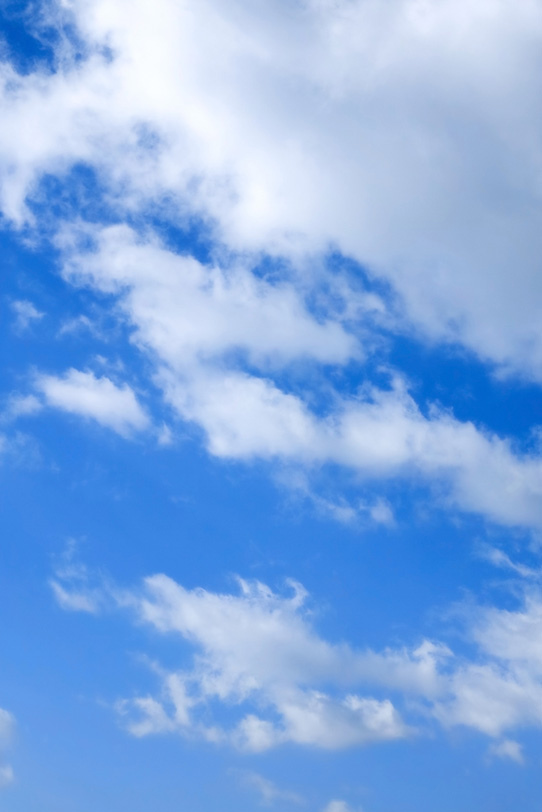 青空に伸びる毛玉のような雲の写真画像