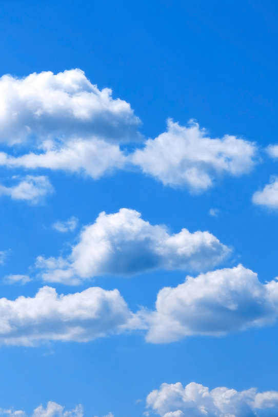 青空にゆっくりと流れる綿雲の写真画像