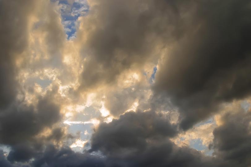 黒い畝雲から溢れる夕焼けの光の写真画像