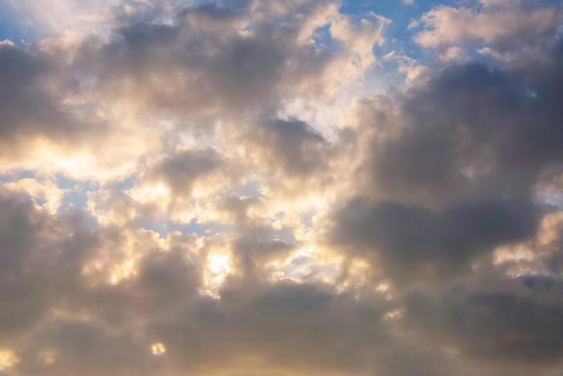 夕日を隔てて輝く夕焼けの雲の写真画像