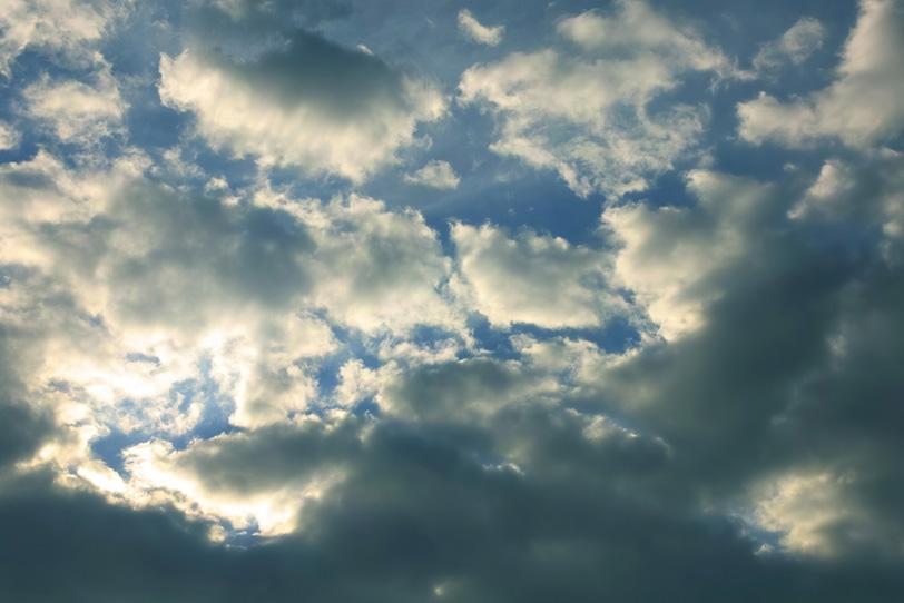 傾く陽に輝く雲と黒い青空の写真画像