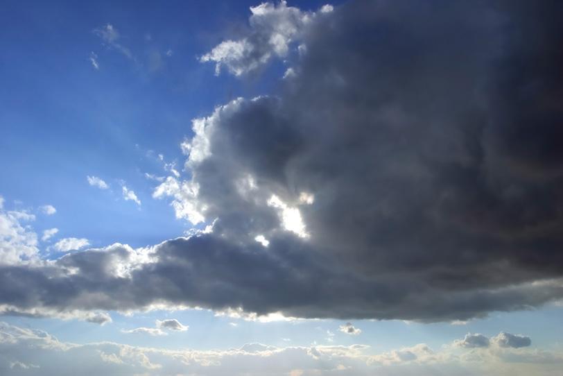 青空と太陽を塞ぐ巨大な層積雲の写真画像