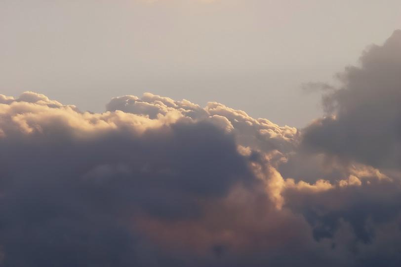 雲の上を照らす淡い夕焼けの光の写真画像