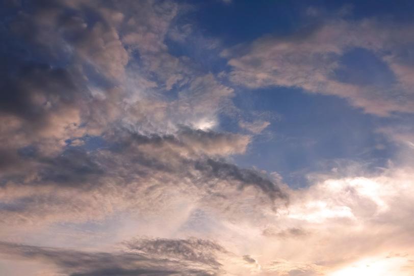 暗い青空を囲む夕焼けの雲の写真画像