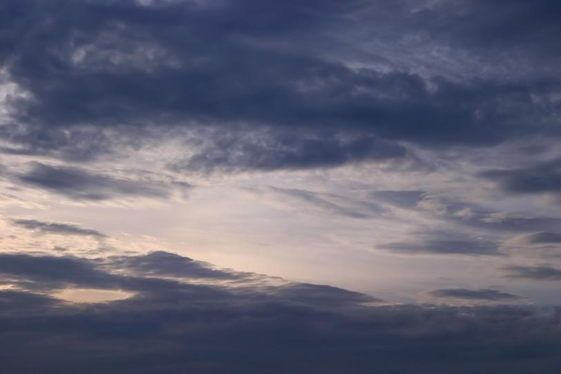 黒曇の間から見える輝く空の写真画像