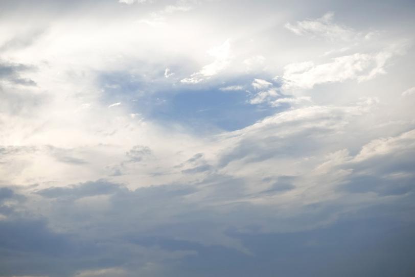 光を浴びて輝く雲から覗く青空の写真画像