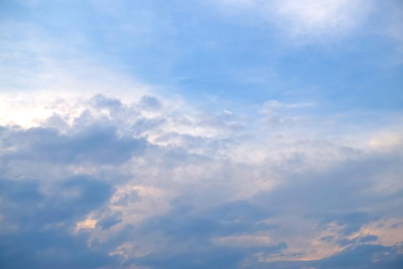 朝焼に淡く染まる雲と青い空の写真画像
