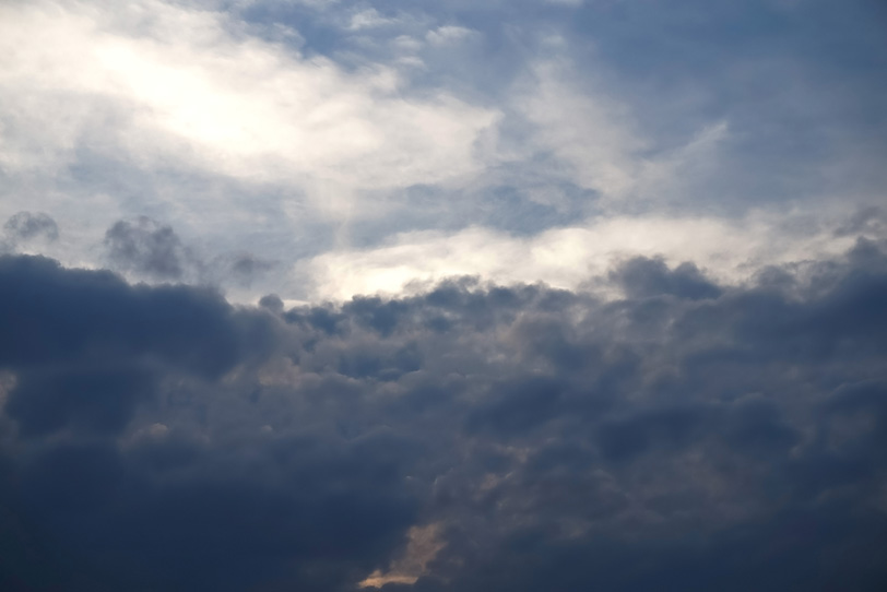 対峙する黒い乱層雲と輝く空の写真画像
